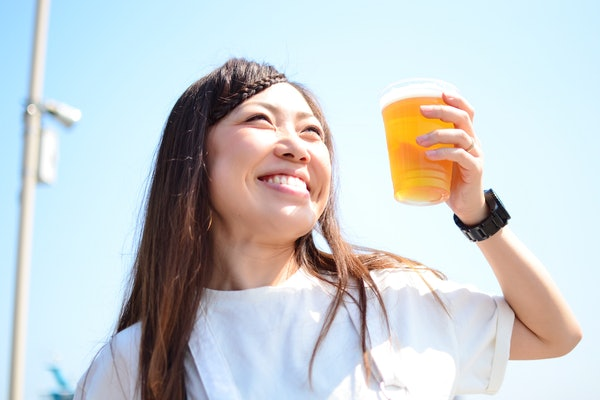 A happy woman in a white T-shirt smiles up at the sky and holds a cup of beer.