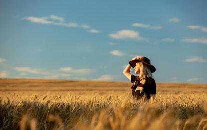 A woman stands in a field of wheat, wondering when Mercury Retrograde is over. Mercury retrograde fa...