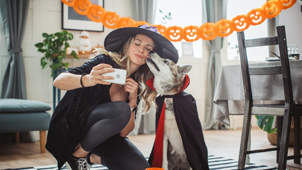 A woman in a witch's hat, black leggings, black Converse, and a black sweater takes a selfie with her dog who's dressed as a vampire.