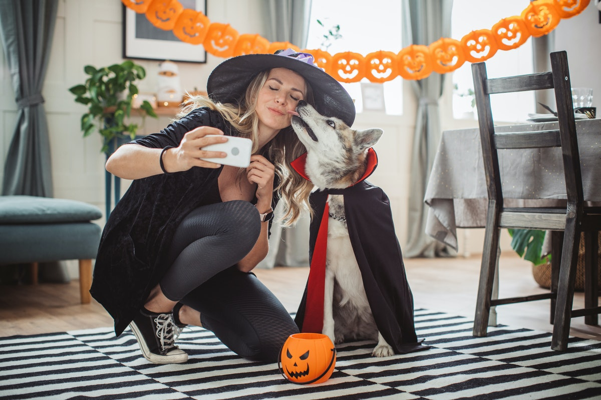 A woman in a witch's hat, black leggings, black Converse, and a black sweater takes a selfie with he...