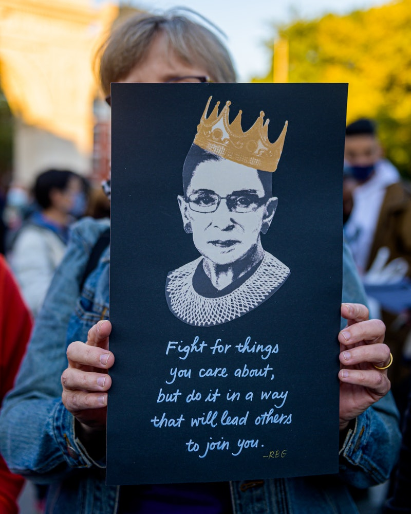 A woman holds up a sign with an image of Ruth Bader Ginsburg at a memorial. Experts explain why fear is a typical grief reaction when someone significant passes away.