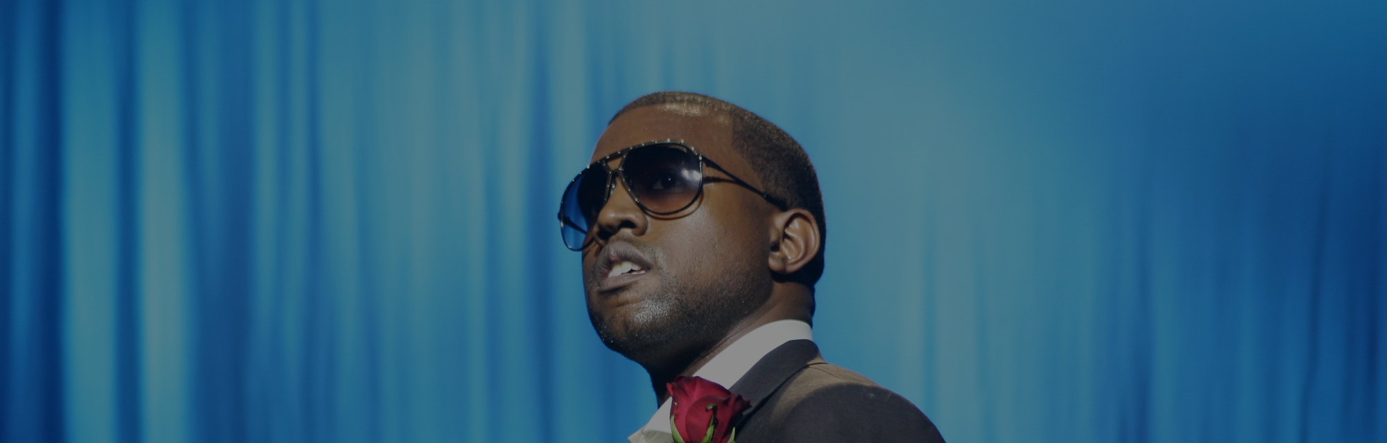 Rapper and artist Kanye West can be seen in a suit with a red handkerchief in his pocket. He is wearing sunglasses and looking upward.