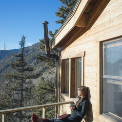 A woman sits on a cabin balcony. Anxiety can take different physical tolls on your body, doctors exp...