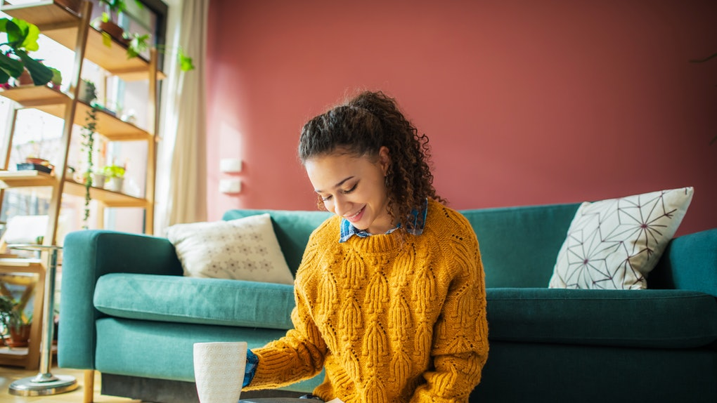 A young Latinx woman wears a yellow sweater and reads a romance novel on the floor of her living room while holding a mug.