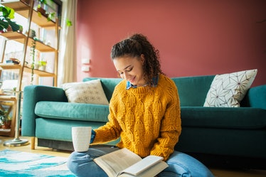 A young Latinx woman wears a yellow sweater and reads a romance novel on the floor of her living roo...