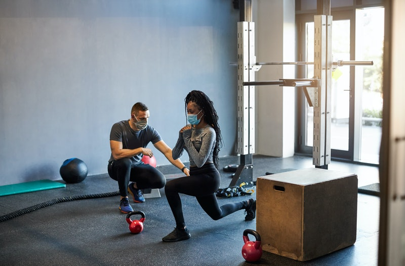 A woman works out with a trainer, both wearing masks. Returning to the gym during COVID feels weirdly normal, trainers and exercisers say.