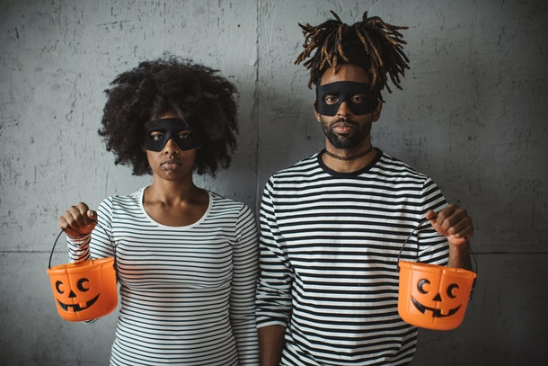 A young couple looks seriously at the camera while holding plastic pumpkin baskets.