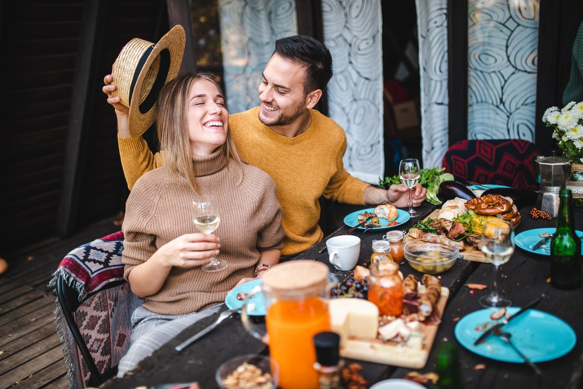 A happy couple enjoys a fall meal out on the porch.