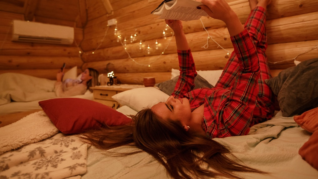 A woman in flannel PJs reads in bed in her cozy cabin room.