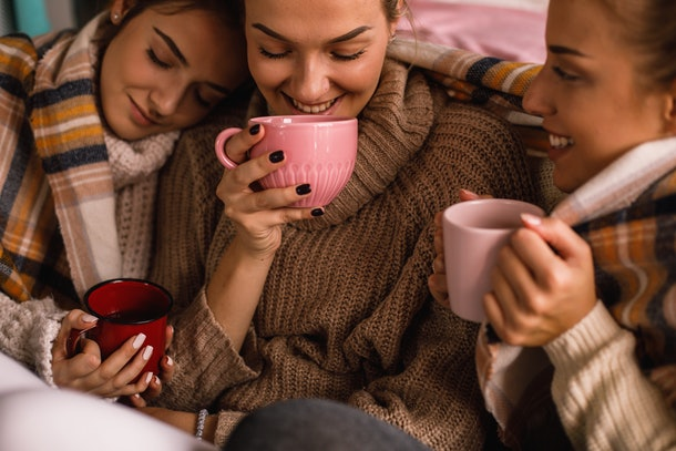 Three women wearing cozy oversized sweaters hold up their coffee mugs and cuddle.