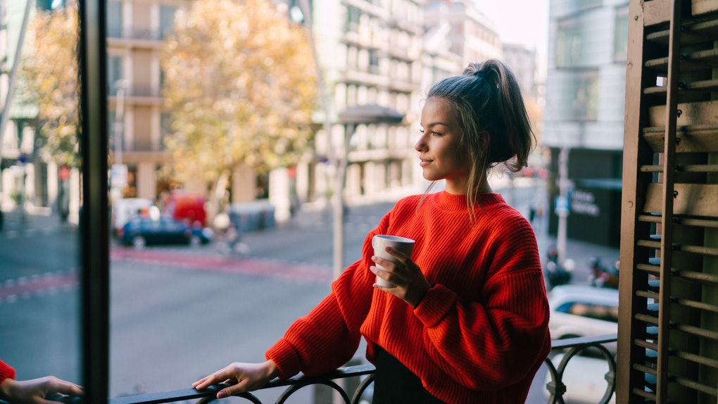 A woman holding a coffee mug on her balcony is dressed in a red turtleneck sweater and black jeans.