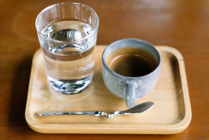 A glass of water and cup of coffee on a light wood tray. What happens to your brain when you stop drinking alcohol? Experts explain.