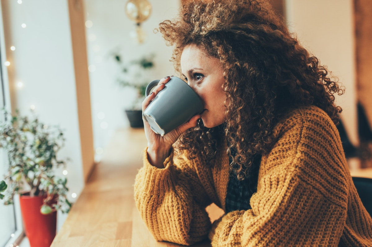 A woman in a gold sweater sips a black mug in a bright coffee shop while looking out the window.