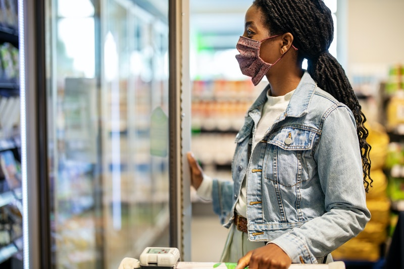 A woman wearing a jacket and mask opens a fridge door at a grocery store. Doctors explain how the second wave of COVID could be different from the first.
