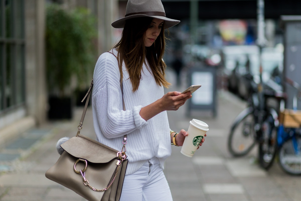 A woman in a felt hat, white sweater, and white jeans holds her Starbucks cup while texting on a cit...