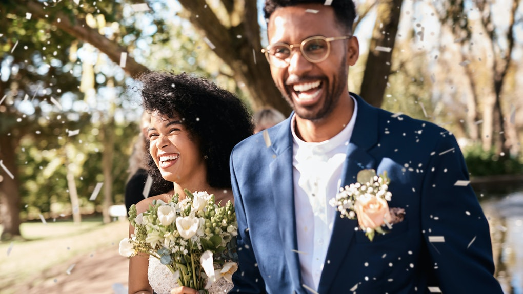 A young Black couple smile while walking through confetti after getting married in their backyard.