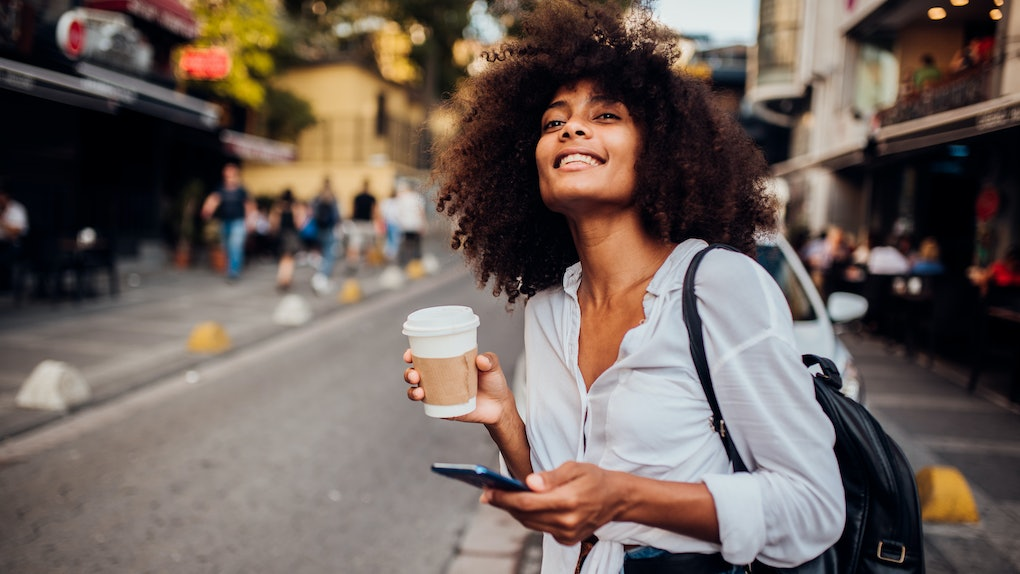 A happy, trendy woman dressed in a white button-down, blue jeans, and black leather backpack looks down the street with a coffee cup in hand.