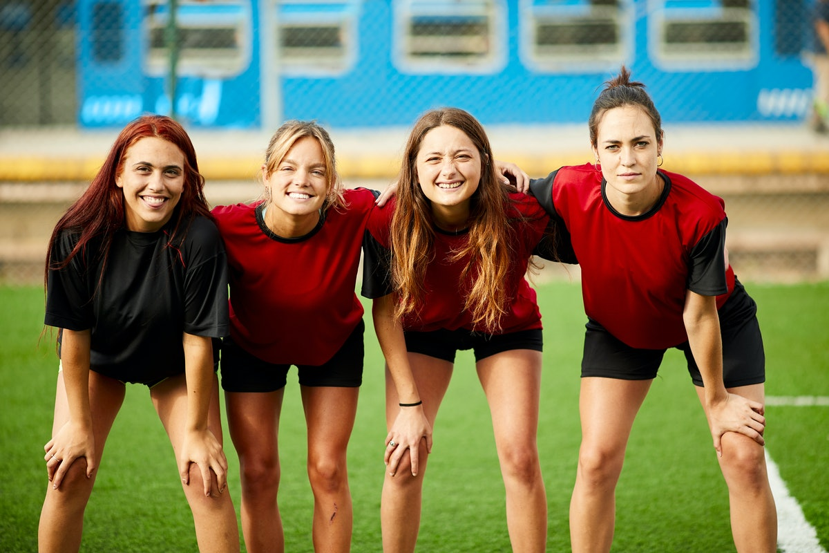 A group of women wearing sports uniforms stand together on the field.