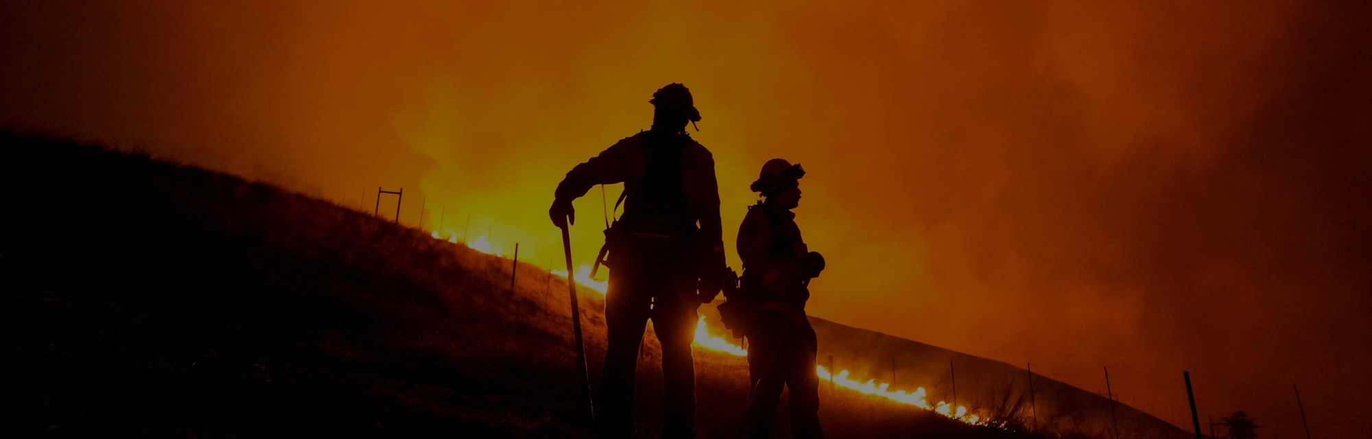 Two firefighters can be seen amid wildfires in California.
