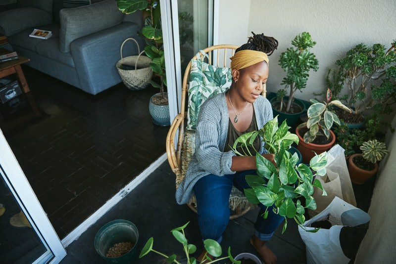 A woman gardens on a balcony. If you're going through intense mood swings, experts say pandemic stress could be to blame.