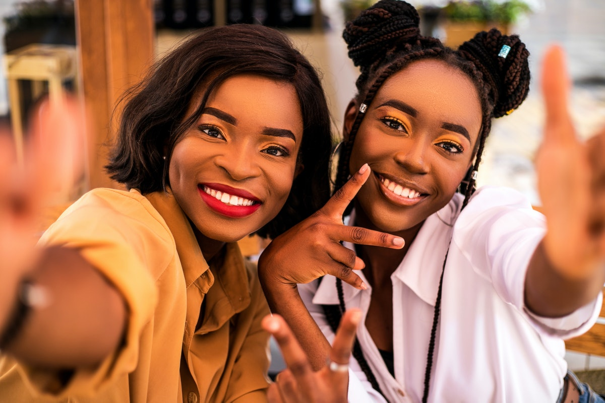 Two young Black women pose for a selfie after reuniting.