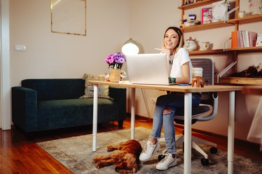 A young woman sits at a desk in her home office that she decorated all cozy for fall.
