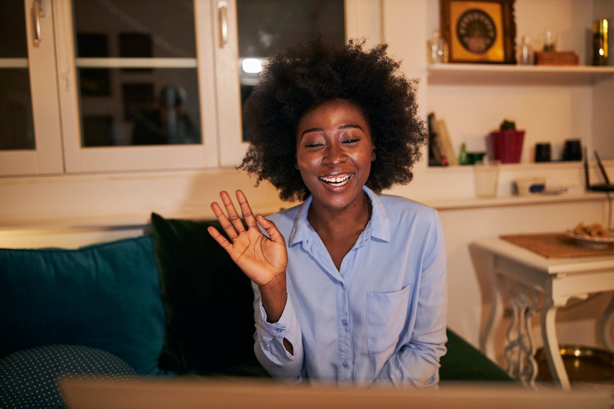 A young Black woman waves at her laptop while video chatting with her long-distance best friend.