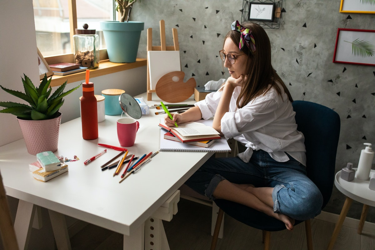 A girl sits crossed legged at her desk, studying a book.