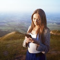 Woman looking at her phone out in nature.