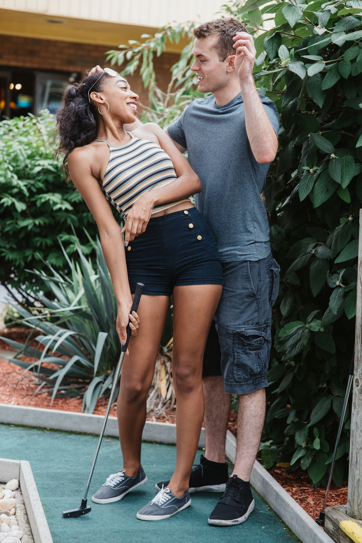 A young couple laughs while playing mini golf in the middle of summer.