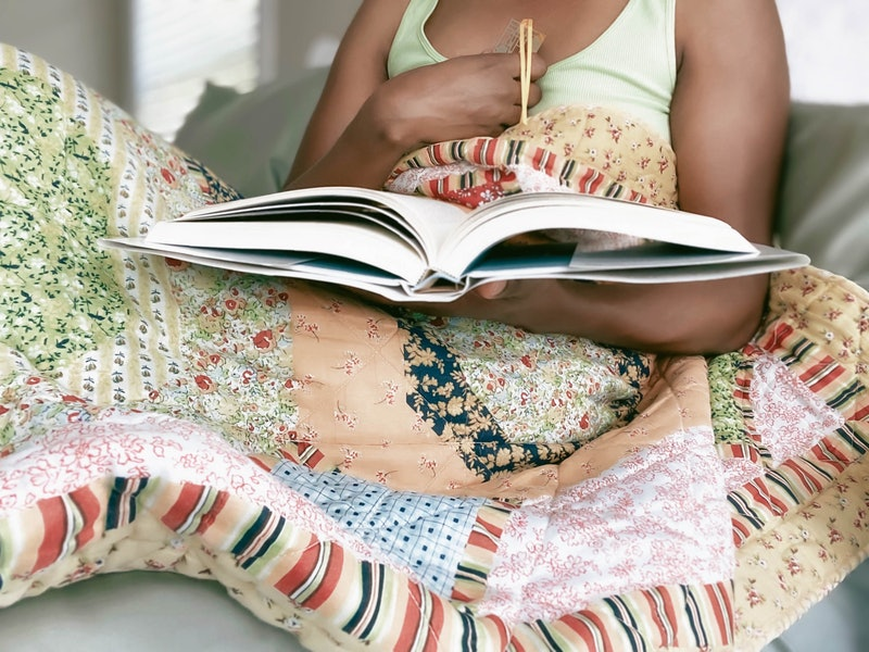 A woman reads a book under a quilt, her hand on her chest. Patients & experts explain how covid-19 can affect mental health.