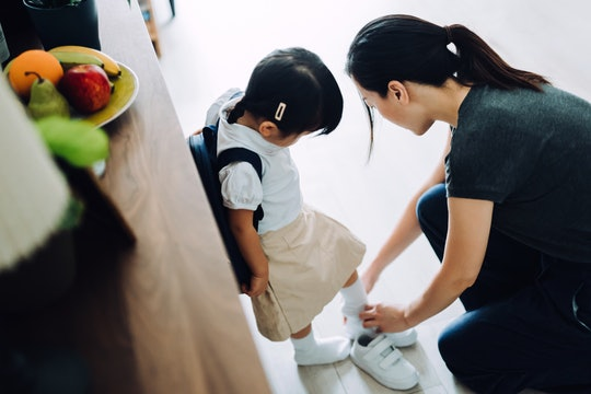 mom putting daughter's shoe on for first day of school