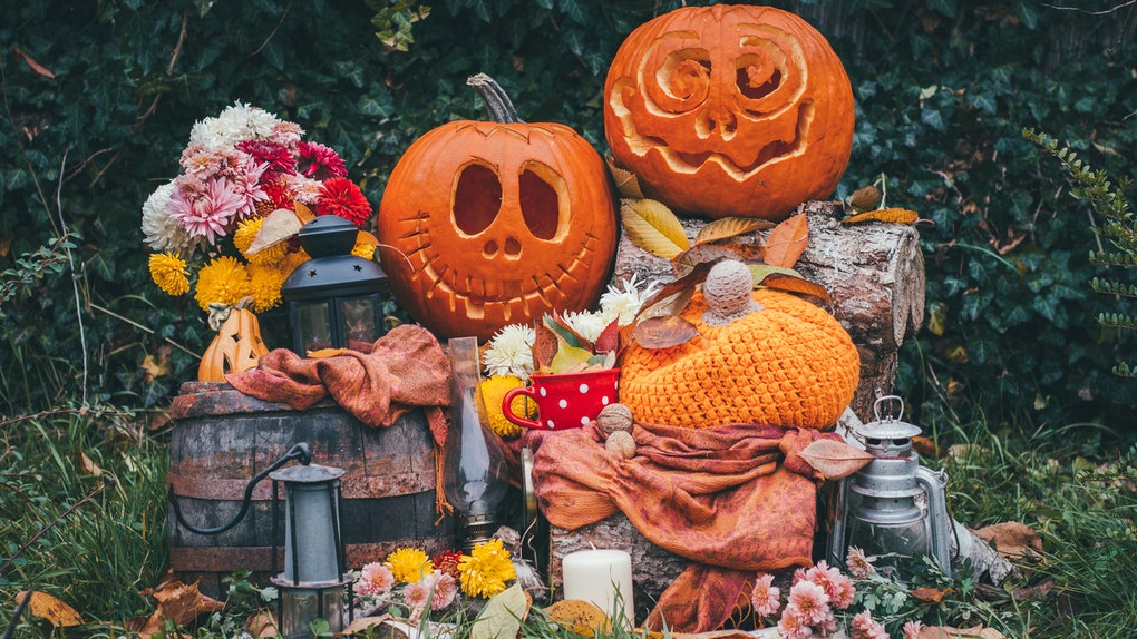 Two jack-o-lanterns are placed on a rustic setup with flowers, lanterns, fall leaves, and a blanket.