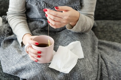 A woman makes tea to soothe her sore throat. Doctors explain what to know about how common sore throats are in COVID.