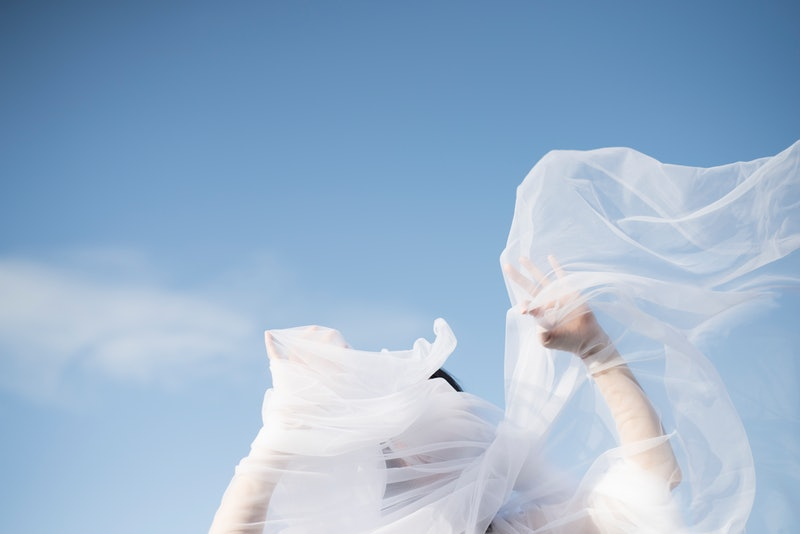 A woman with her hands in a yard of tulle. Here are scientific theories behind how deja vu works.