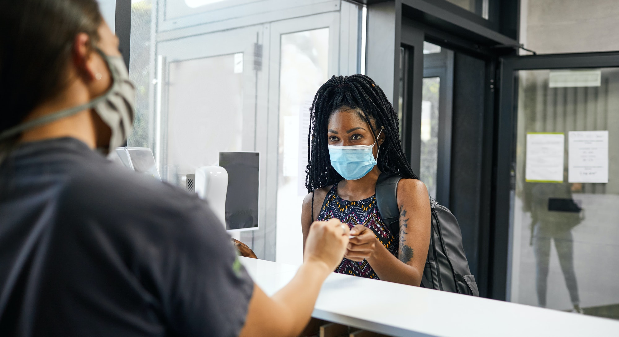 A person with natural hair wears a mask while she checks in to her gym. Even if you feel safe going back to the gym, it's not going to be business as usual.