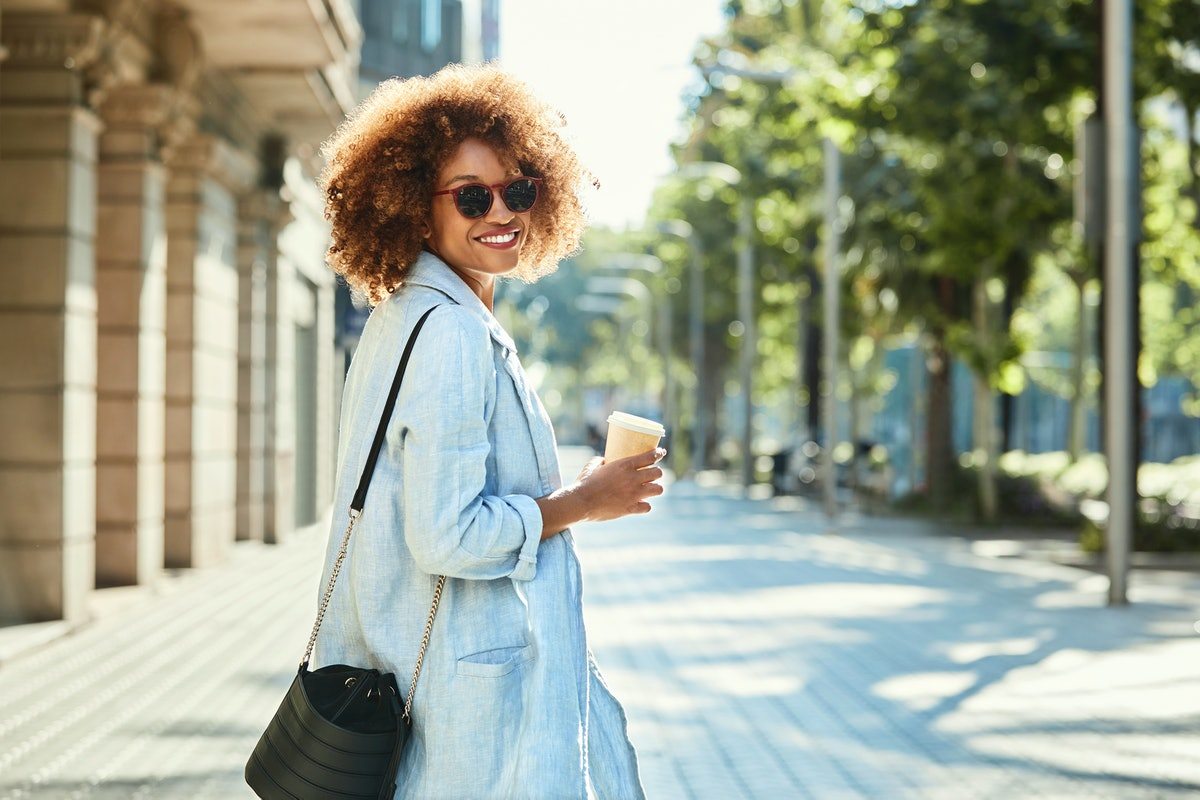 A happy Black woman dressed in a long coat and sunglasses holds a coffee cup and smiles as she looks back on a sidewalk.