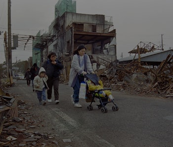 Aftermath of 1995 earthquake, family in street surrounded by rubble