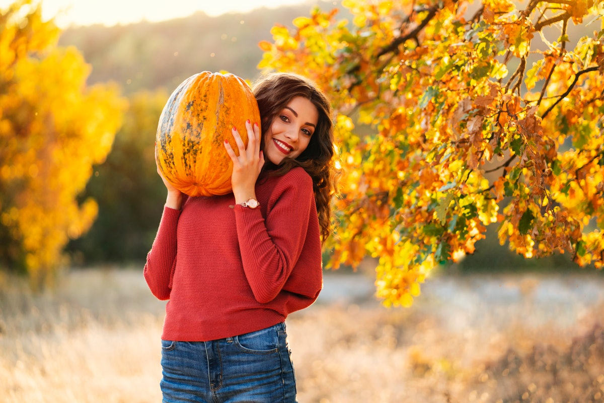 A brunette woman in a red sweater and jeans holds a pumpkin and smiles while standing in a sunny field.