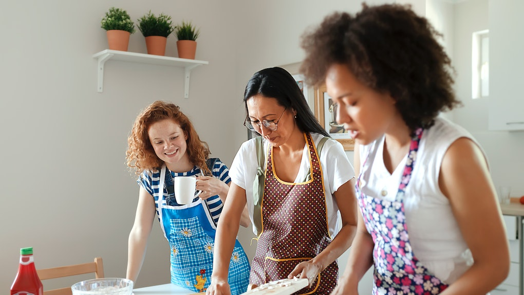 Three women in aprons make pizza in a bright kitchen.