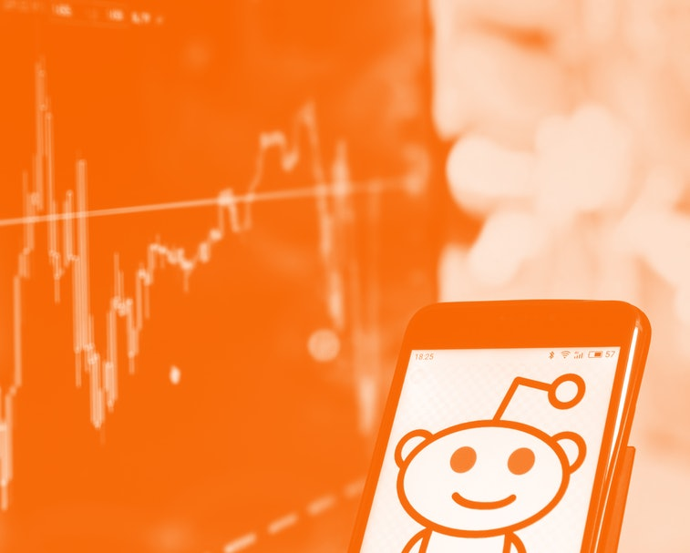 The logo for Reddit is seen on a smartphone. It is a friendly alien with one antenna smiling. The background portrays unspecified stock spikes.