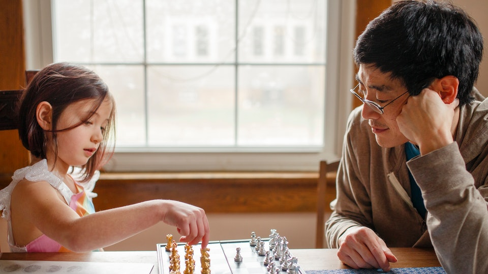 girl and dad playing chess