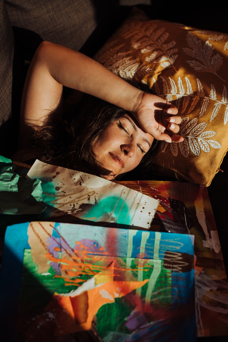 A woman sleeps underneath colorful prints. Sleep experts officially called for an end to daylight savings in a position paper.