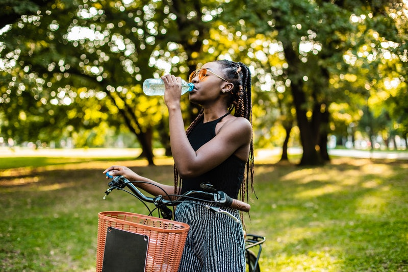A woman drinks water while on a bike. Sober september is a reset of your drinking habits.