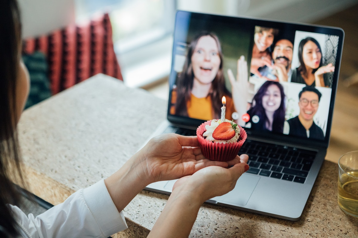 A young woman shows off her birthday cupcake to her friends who she's video chatting with.