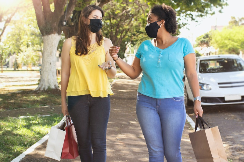Two friends walk with groceries while wearing masks. A small gathering during the coronavirus pandemic isn't risk-free; here's how to stay safe.