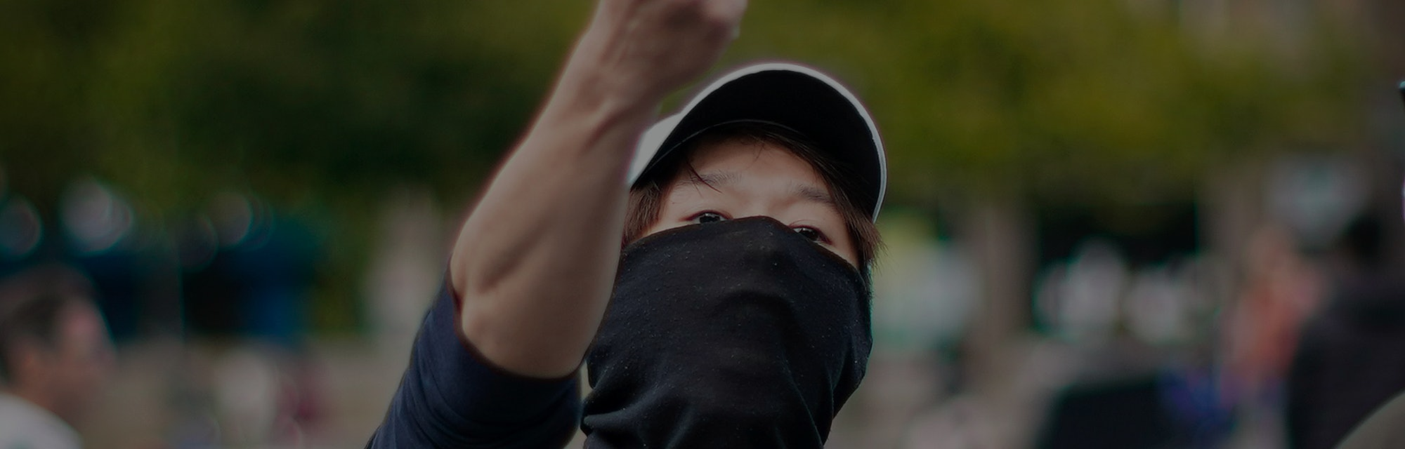 A protester in Hong Kong can be seen with a white hat and black face covering that hides the lower half of his face. He is showing someone his middle finger in anger.