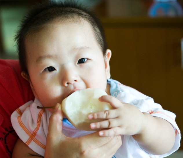 asian baby eating a pear