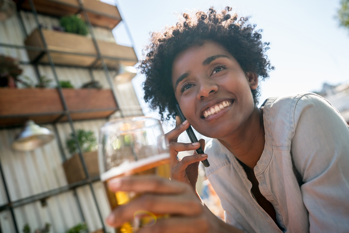 A young woman sits outside her apartment building and holds a beer while talking on the phone.