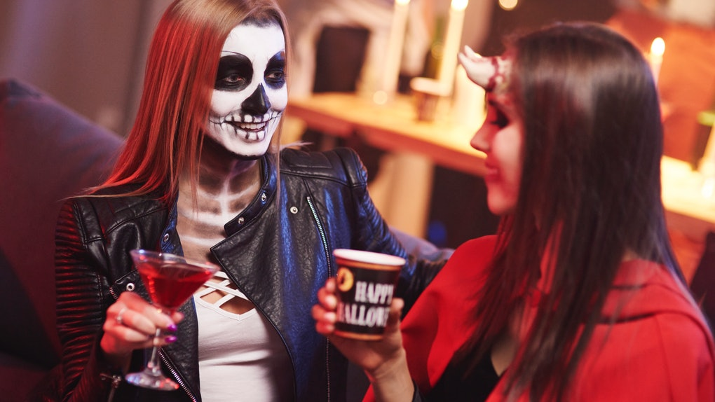 Friends enjoy cocktails at a Halloween party, while dressed up like a skeleton and devil.